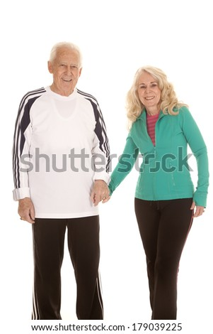 an elderly couple holding hands walking with smiles on their faces. - stock photo