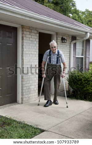 An elderly disabled veteran with crutches, with a smiling happy face, standing alone outside of his tiny apartment. - stock photo