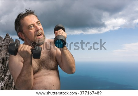 An elderly fat and wet man exercising with dumbbells against nature background with sea and cloudy sky - stock photo