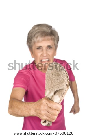 An elderly grandma shows who is boss as she threatens you with her old slipper. - stock photo