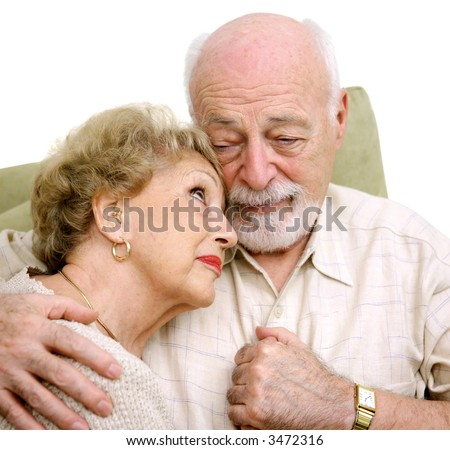 An elderly husband and wife consoling themselves over the loss of a loved one. - stock photo
