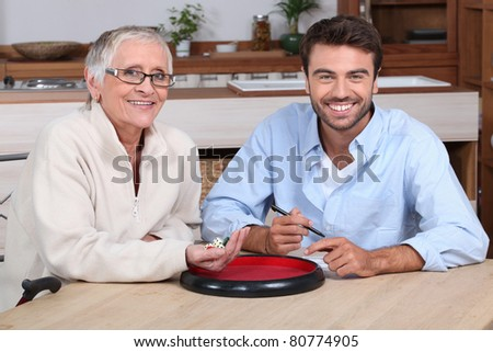 An elderly lady and a young bearded man playing dice and looking at us. - stock photo