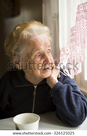 An elderly lady sitting near the window in the kitchen. - stock photo