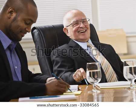 An elderly man and a young businessman are seated together at a desk in an office.  They are laughing and looking away from the camera.  Horizontally framed shot. - stock photo