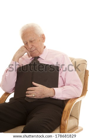 An elderly man falling asleep with a book on his chest. - stock photo