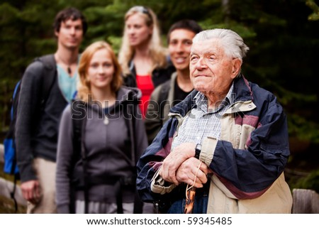An elderly man giving a tour for a young group of people