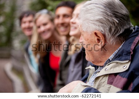 An elderly man guiding a group of young people in the forest - stock photo