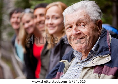 An elderly man in front of a group of young people - stock photo