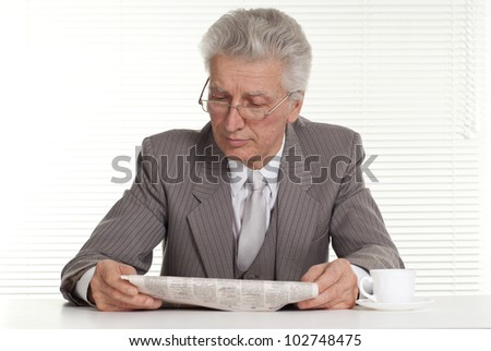 An elderly man in glasses sitting on a white background