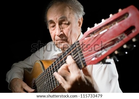 An elderly man in white shirt playing an acoustic guitar. Dark background. - stock photo