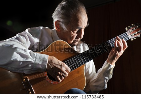 An elderly man in white shirt playing an acoustic guitar. Dark background.