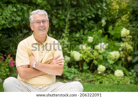 An elderly man is crossing his arms and smiling - stock photo