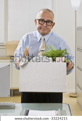 An elderly man is in an office and is holding a box of personal belongings. He is looking at the camera.  Vertically framed shot.. - stock photo