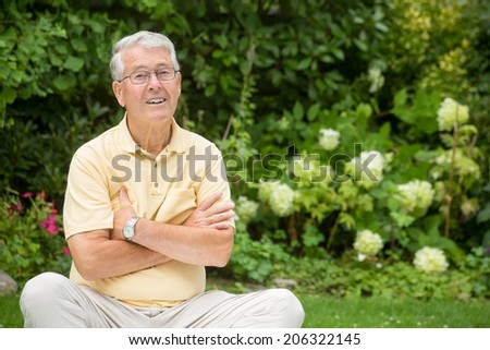 An elderly man is lifting his eyebrows with his arms crossed - stock photo