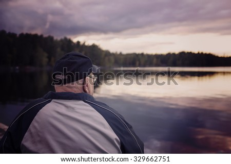 An elderly man is looking at the sea while sitting on a bench. He is remembering the old times and wearing a cap and a jacket. The man is composed on the left. Image has a vintage effect applied. - stock photo