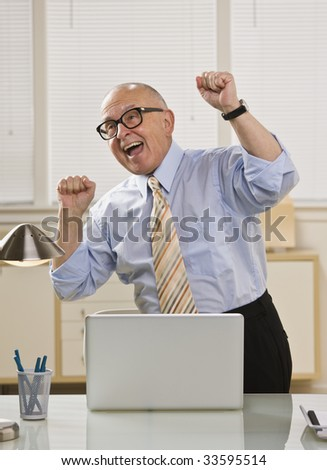 An elderly man is looking very excited while he works on his laptop.  He is looking away from the camera.  Vertically framed shot. - stock photo