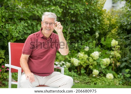 An elderly man is showing something small - stock photo