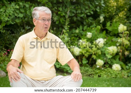 An elderly man is sitting relaxed in a garden while resting his arms on his knees and is upset - stock photo