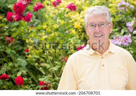 An elderly man is smiling into the camera with a beautiful rose background - stock photo
