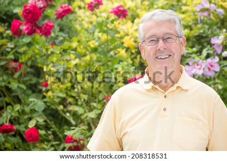 An elderly man is smiling straight into the camera with a beautiful rose background - stock photo