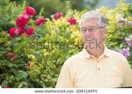 An elderly man is smiling while turning left with a beautiful rose background - stock photo