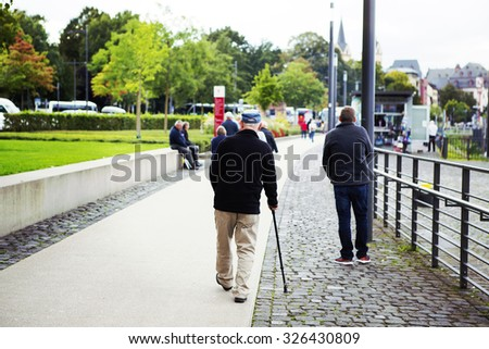 An elderly man is walking in the park with a walking stick. Some unidentified person are walking and sitting also. Image has a vintage effect applied. - stock photo