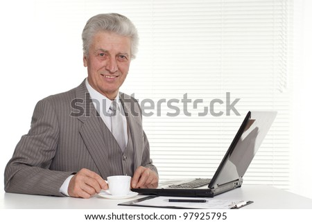 an elderly man sitting at the computer on a light