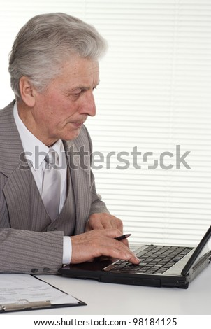 an elderly man sitting at the computer on a light background