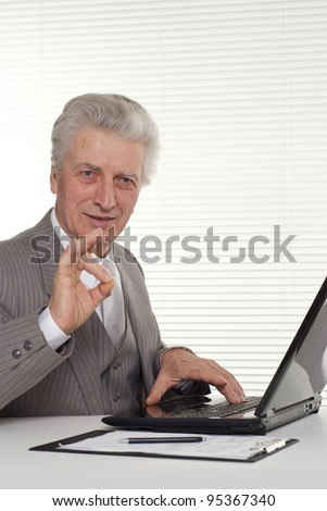 an elderly man sitting at the laptop on a white