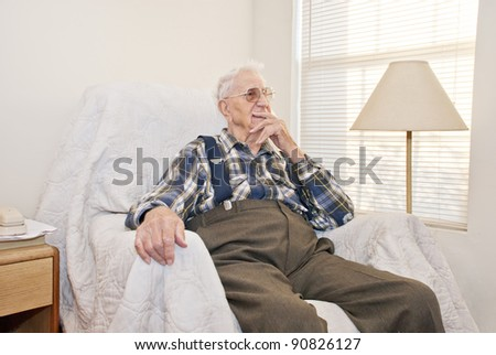 An elderly man sitting by a window in an old chair deep in thought