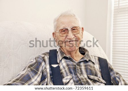 An elderly man sitting in a chair at his home, closeup with copy space