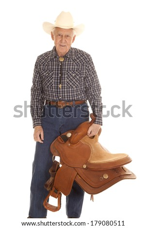 An elderly man standing holding a saddle in his hand. - stock photo
