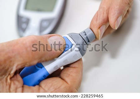 An elderly man takes a drop of blood to measure his blood sugar level at home. The picture depicts drawing a drop of blood. The blood sugar measuring device is visible in the background - stock photo
