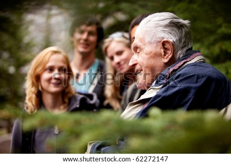 An elderly man telling stories to a group of young people
