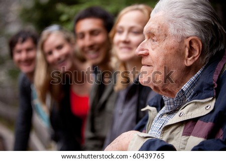 An elderly man telling stories to a group of young people in the forest - stock photo
