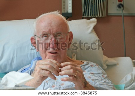 An elderly man tries to explain what it's like to stay in a hospital. - stock photo