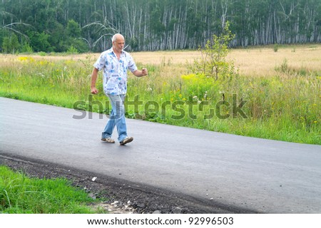 An elderly man walking along the road in the summer in the countryside, Moscow region