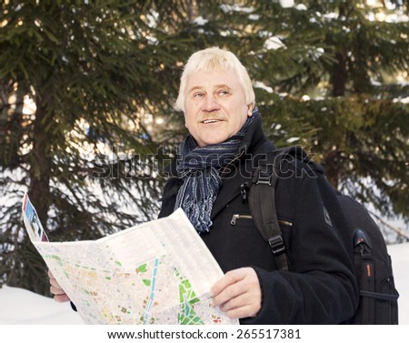 an elderly man with a map and a backpack in the winter - stock photo