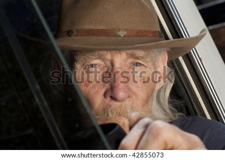 An elderly man with a white beard driving a pickup truck and staring out the window - stock photo