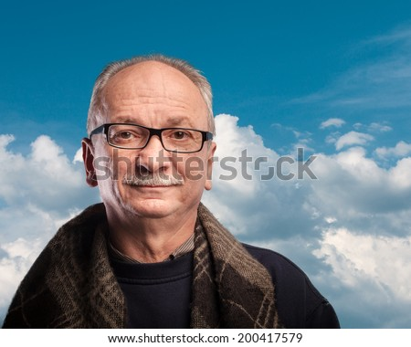 An elderly man with glasses looks skeptically - stock photo