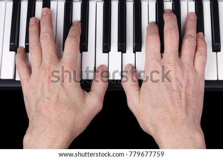 An elderly retired man plays an old melody on the keyboard of the synthesizer. Studio human eyes view  shot. Partially isolated on black with patch