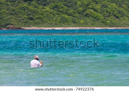 An elderly senior citizen snorkels in tropical waters in the Caribbean off of the gorgeous tropical Puerto Rican island of Culebra. - stock photo