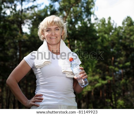 An elderly woman after exercising in the forest holding a bottle of water - stock photo