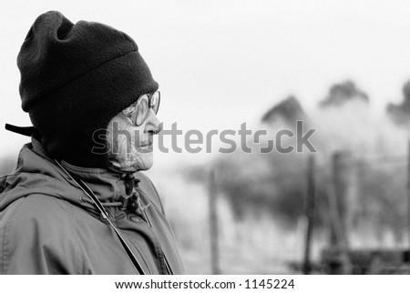 An elderly woman, dressed in winter clothes and hat, stares off into the distance.