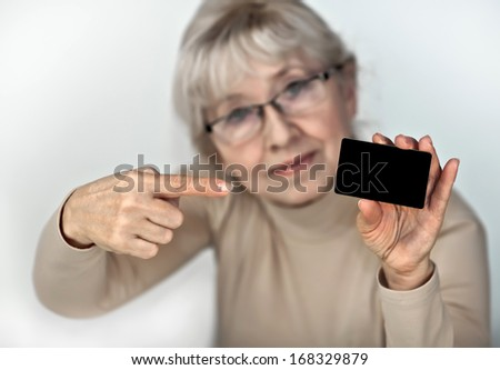 An elderly woman holding a plastic card - stock photo
