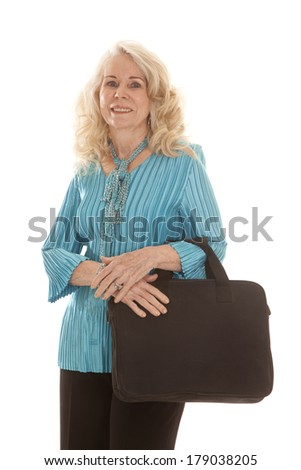an elderly woman holding on to her computer bag with a smile on her face.