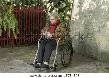 An elderly woman is sitting in a wheelchair in her garden.  She is looking down at a notepad and writing something on it.  Horizontally framed shot.