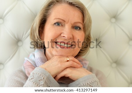 an elderly woman looks straight and smiling - stock photo