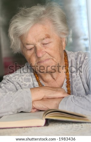 An elderly woman reading a book