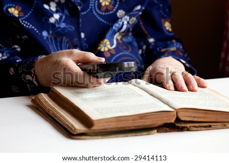 An elderly woman reading a very old book - stock photo